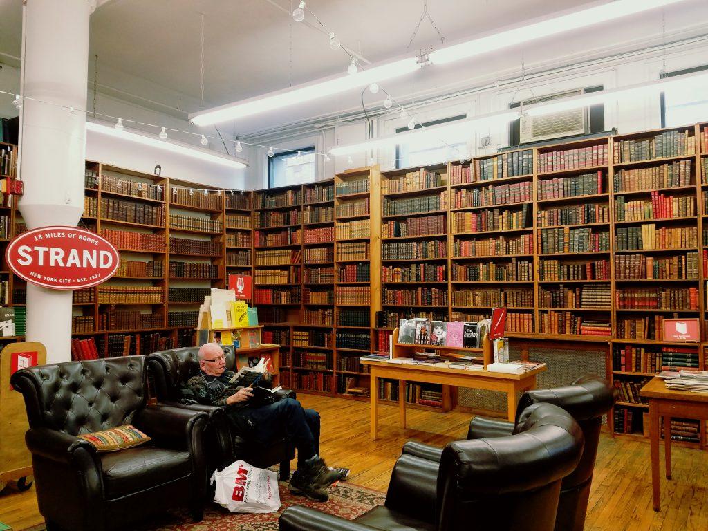 Um senhor aproveita as únicas poltronas disponíveis na livraria. Elas ficam na sala de livros raros.